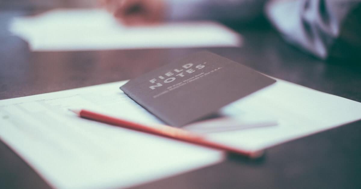 机の上に置かれたメモ帳の画像